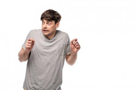 Photo pour Jeune homme effrayé regardant loin et gesticulant isolé sur le blanc - image libre de droit