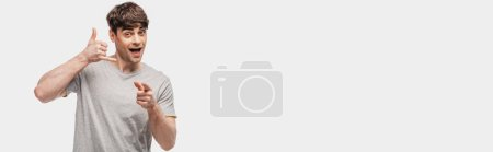 Photo for Panoramic shot of cheerful young man pointing with finger at camera and showing lets drink gesture isolated on grey - Royalty Free Image
