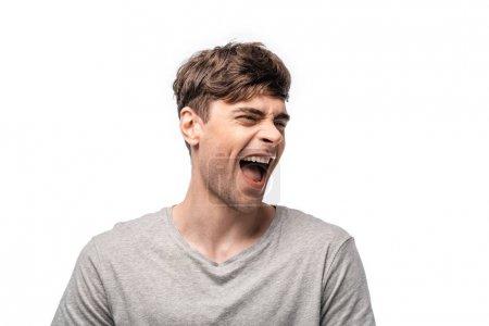 Photo pour Jeune homme excité riant tout en regardant loin isolé sur le blanc - image libre de droit