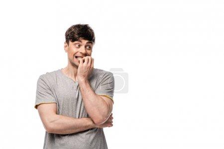 Photo pour Jeune homme effrayé regardant loin tout en retenant la main près du visage d'isolement sur le blanc - image libre de droit