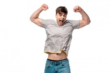 Photo pour Jeune homme excité affichant le geste gagnant tout en regardant l'appareil-photo isolé sur le blanc - image libre de droit