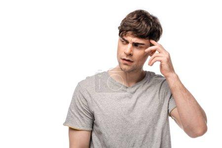 Photo pour Jeune homme pensif regardant loin tout en retenant la main près de la tête d'isolement sur le blanc - image libre de droit