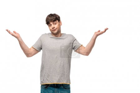 Photo for Discouraged young man showing shrug gesture while looking at camera isolated on white - Royalty Free Image