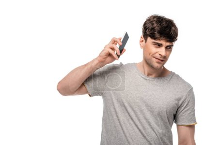 Photo for Positive young looking away while talking on smartphone isolated on white - Royalty Free Image