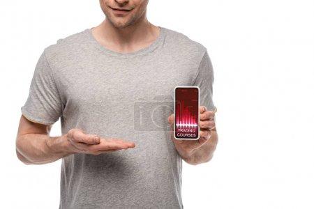 Photo pour Vue recadrée de l'homme présentant le smartphone avec l'application de cours de négociation, d'isolement sur le blanc - image libre de droit