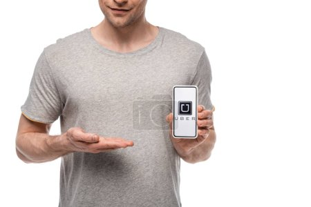 Photo for KYIV, UKRAINE - MAY 16, 2019: cropped view of man presenting smartphone with uber app, isolated on white - Royalty Free Image