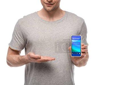 Photo pour Vue recadrée de l'homme présentant le smartphone avec l'application de réservation, d'isolement sur le blanc - image libre de droit