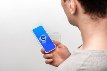 Photo for KYIV, UKRAINE - MAY 16, 2019: cropped view of man using smartphone with shazam app, isolated on grey - Royalty Free Image