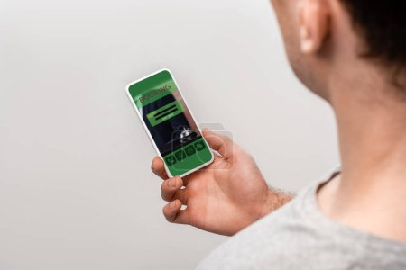 Photo pour Vue recadrée de l'homme utilisant le smartphone avec l'application de réservation, d'isolement sur le gris - image libre de droit