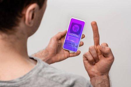 Photo pour Vue recadrée de l'homme utilisant le smartphone avec l'application d'achat et affichant le doigt moyen, isolé sur le gris - image libre de droit