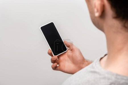 Photo for Cropped view of man holding smartphone with blank screen isolated on grey - Royalty Free Image