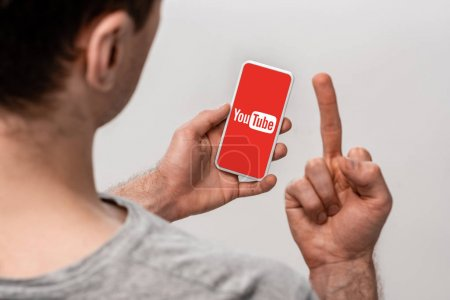 Photo for KYIV, UKRAINE - MAY 16, 2019: cropped view of man using smartphone with youtube app and showing middle finger, isolated on grey - Royalty Free Image