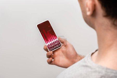 Photo pour Vue recadrée de l'homme utilisant le smartphone avec l'application de cours de négociation, d'isolement sur le gris - image libre de droit