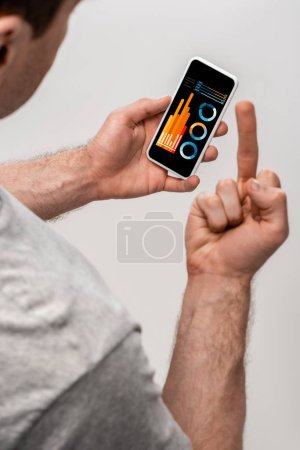 Photo for Cropped view of man using smartphone with infographic app and showing middle finger, isolated on grey - Royalty Free Image