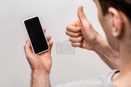 Photo pour Vue partielle de l'homme montrant pouce levé tout en tenant smartphone avec écran vide isolé sur gris - image libre de droit