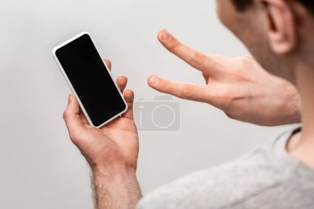 Photo for Cropped veiw of man showing victory sign while holding smartphone with blank screen isolated on grey - Royalty Free Image