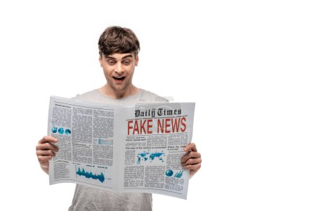 Photo for Cheerful handsome man reading newspaper with fake news isolated on white - Royalty Free Image