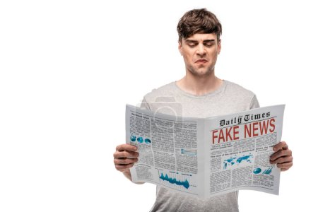 Photo for Dissatisfied young man reading newspaper with fake news isolated on white - Royalty Free Image