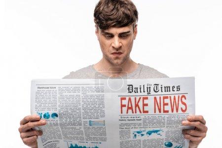 Foto de Joven disgustado leyendo periódico con noticias falsas aisladas en blanco - Imagen libre de derechos