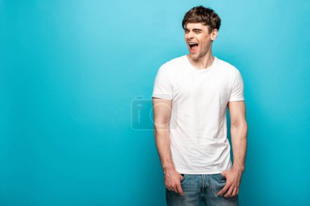 Photo for Handsome young man laughing while looking away on blue background - Royalty Free Image