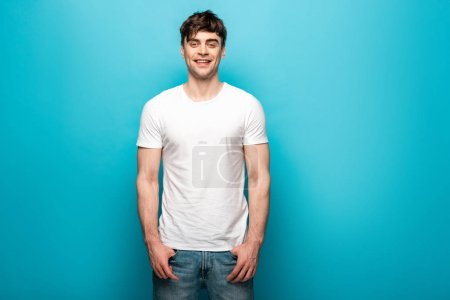 Foto de Handsome young man in white t-shirt smiling at camera on blue background - Imagen libre de derechos