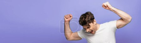 Photo for Panoramic shot of happy young man showing winner gesture isolated on blue - Royalty Free Image