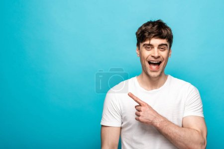 Photo for Cheerful young man pointing with finger and looking at camera on blue background - Royalty Free Image