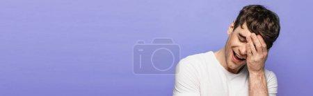 Photo pour Tir panoramique de l'homme pur souriant avec les yeux fermés tout en retenant la main sur le visage isolé sur le bleu - image libre de droit