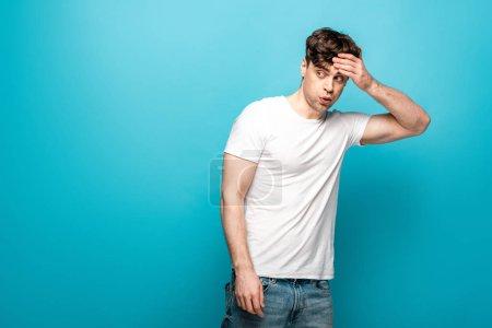 Photo pour Jeune homme choqué regardant loin tout en retenant la main sur la tête sur le fond bleu - image libre de droit