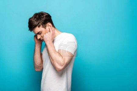 Photo pour Jeune homme épuisé branchant des oreilles avec des doigts sur le fond bleu - image libre de droit