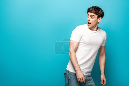 Photo pour Scared young man in white t-shirt looking back on blue background - image libre de droit