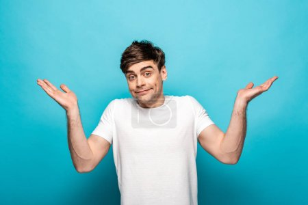 Photo for Disappointed young man looking at camera and showing shrug gesture on blue background - Royalty Free Image