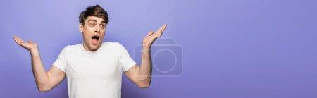 Photo pour Tir panoramique de l'homme beau affichant le geste de haussement d'épaules sur le fond bleu - image libre de droit