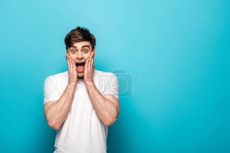 Photo for Excited young man holding hands near face while looking at camera on blue background - Royalty Free Image