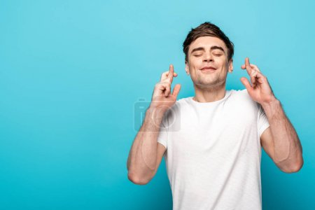 Photo for Positive young man holding crossed fingers with closed eyes on blue background - Royalty Free Image