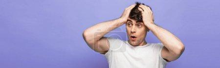 Photo pour Tir panoramique de jeune homme choqué retenant des mains sur la tête et regardant loin sur le fond bleu - image libre de droit