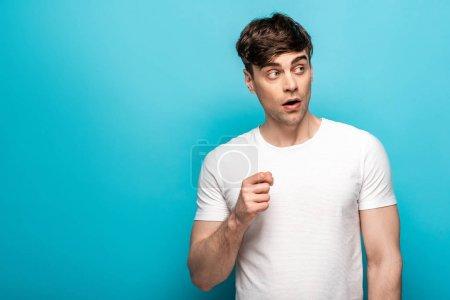 Photo pour Jeune homme pensif dans le t-shirt blanc regardant loin sur le fond bleu - image libre de droit