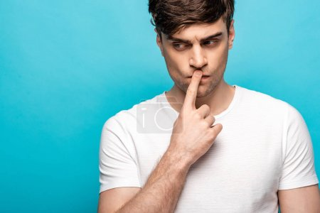 Photo for Thoughtful man showing silence sign while looking away isolated on blue - Royalty Free Image