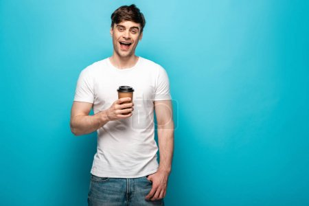 Photo for Positive young man smiling at camera while holding disposable cup on blue background - Royalty Free Image