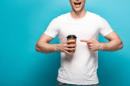 Photo for Cropped view of smiling man pointing with finger at paper cup on blue background - Royalty Free Image