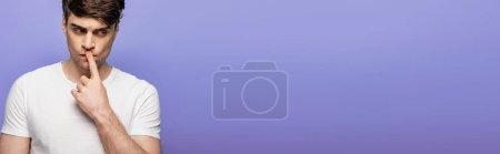 Photo pour Tir panoramique du jeune homme pensif affichant le geste de silence d'isolement sur le bleu - image libre de droit