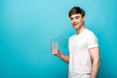 handsome young man showing smartphone with blank screen and smiling at camera on blue background