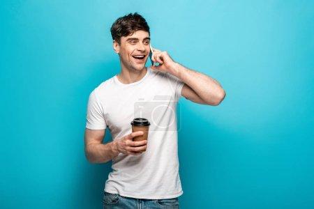 Photo pour Jeune homme de sourire parlant sur le smartphone tout en retenant le café pour aller et regardant loin sur le fond bleu - image libre de droit