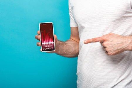 Photo pour Vue recadrée de l'homme pointant au smartphone avec l'application de cours de négociation, d'isolement sur le bleu - image libre de droit