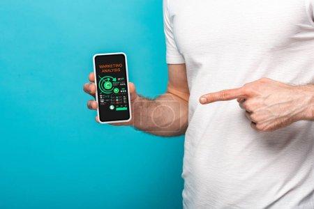 Photo pour Vue recadrée de l'homme pointant vers le smartphone avec l'application d'analyse de marketing, d'isolement sur le bleu - image libre de droit