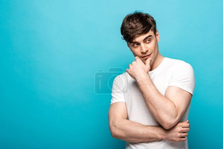 Photo pour Pensive young man looking away while holding hand near face on blue background - image libre de droit