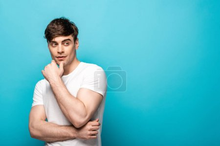 Photo for Dreamy young man looking away while holding hand near face on blue background - Royalty Free Image