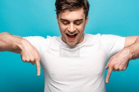 Photo pour Jeune homme ringard pointant vers le bas avec des doigts sur le fond bleu - image libre de droit