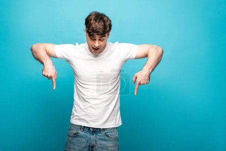 Photo for Young man in white t-shirt pointing down with fingers on blue background - Royalty Free Image