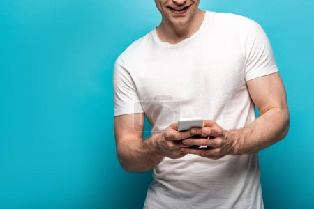 Photo for Cropped view of smiling young man using smartphone on blue background - Royalty Free Image